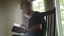 young man sitting reading a Bible