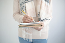a woman holding a journal and pen