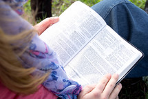 a woman reading a Bible in her lap outdoors