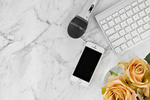 iPhone, microphone, computer keyboard, and yellow roses on a marbled background