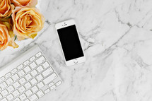 cellphone, computer keyboard, and yellow roses on a marbled background