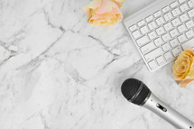 microphone, computer keyboard, and yellow roses on a marbled background