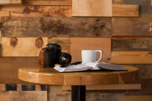 An open Bible, coffee cup, and camera on a round table.