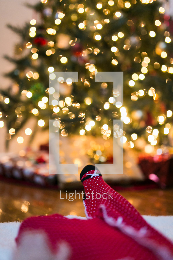 baby lying under a Christmas tree