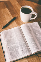 An open Bible and a cup of coffee on a table.
