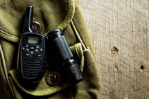 flashlight and hand-held radio on a green bag