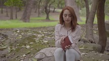 a woman reading a Bible in a park