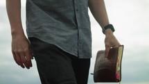 a man walking on a beach carrying a Bible