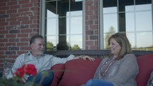 a husband and a wife talking on a porch