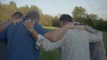men's group praying outdoors