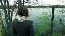 a girl standing looking out at a lake