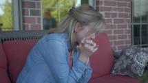 a woman praying on a porch