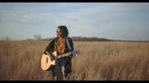 a woman standing in a field holding a guitar and singing