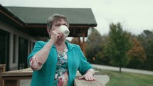 senior woman on a deck with a cup of coffee