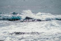 Ocean waves crashing upon rocks.