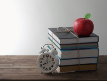 books with alarm and red Apple