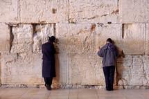 Men praying at the Western Wall at night.