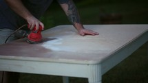 a man sanding a table