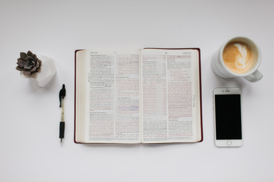open Bible and other items on a desk