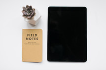 succulent plant, field notes book, and iPad