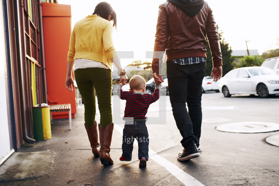 mother, father, and toddler son walking together holding hands