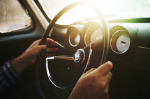 man's hands on a steering wheel