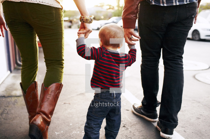 mother, father, and toddler walking holding hands