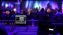 man at a soundboard during a worship service