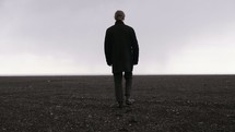 a man walking across a barren flat landscape