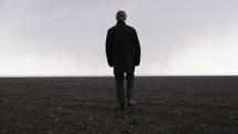 a man walking across a barren flat landscape