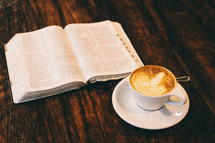 An open Bible and cup of latte' on a rustic wooden table.