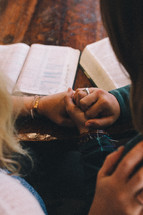 Two women holding hands and praying at a table with open Bibles.