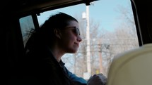 woman riding in the backseat of a car with hair blowing in the wind
