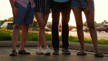legs of a group of friends standing together with arms around each other
