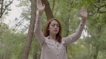 a woman with raised hands standing outdoors