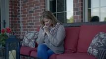 a female praying on a porch