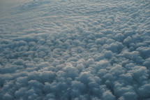 Photograph of a sky full of clouds from an airplane windows portraying the beautiful creation of God's heavens, which can be used as a decorative background or wallpaper for church services and bulletins.