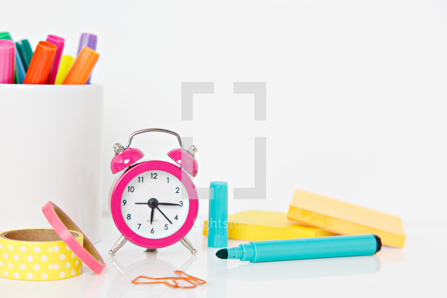 alarm clock, mug of markers, and paperclips on a white background