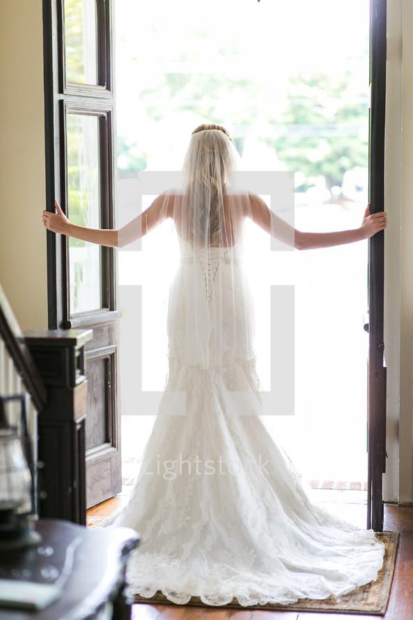 a bride standing in an open doorway