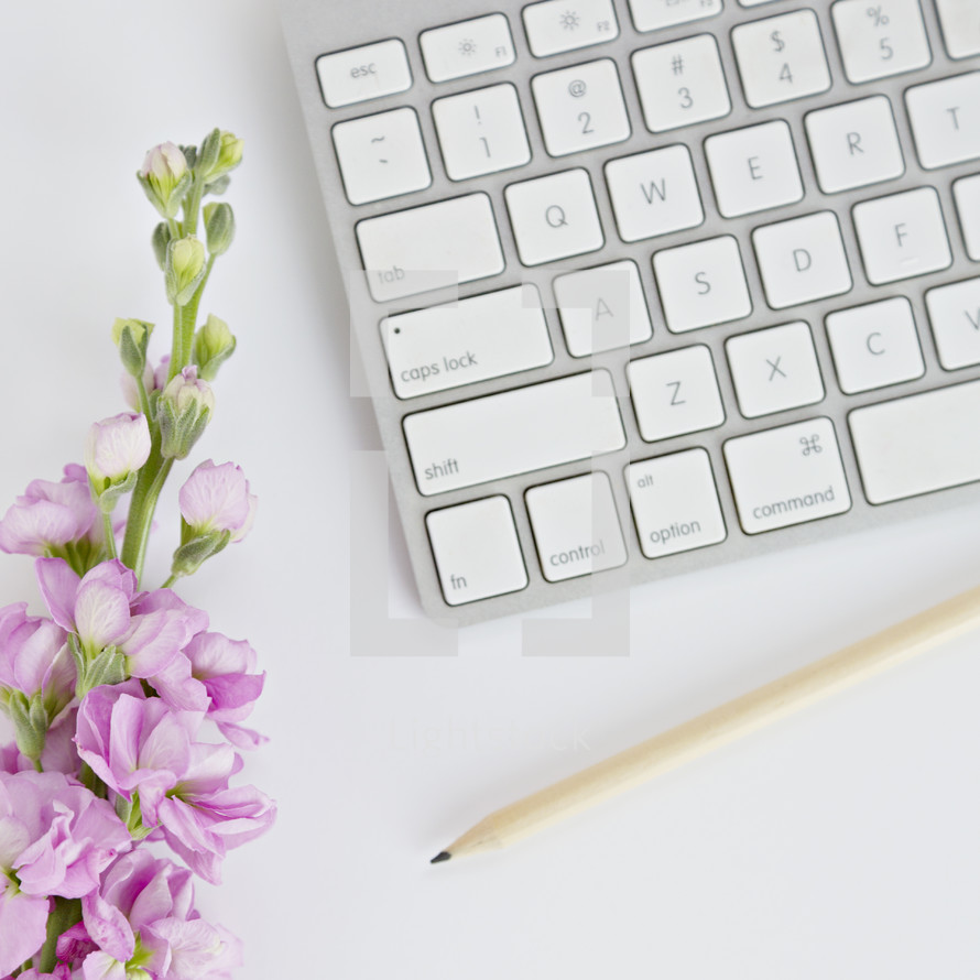 computer keyboard and pencil on a white desk