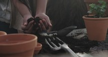 a woman putting potting soil into clay pots