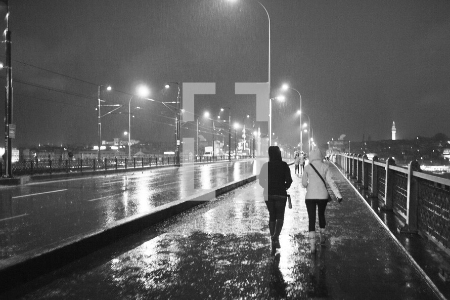 Two people walking over a bridge during a stormy night