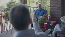 men sitting on a porch talking