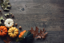 pumpkins and fall leaves on a wood background