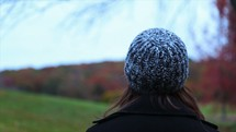 a woman standing and looking out at fall colors