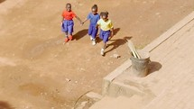 kids walking holding hands in Uganda