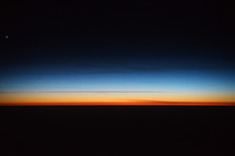 Photograph of a colorful sunrise sky from an airplane windows portraying the beautiful creation of God's heavens, which can be used as a decorative background or wallpaper for church services and bulletins.
