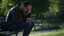 man sitting on a park bench working on his smartphone