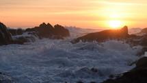 waves crashing into a shore at sunset