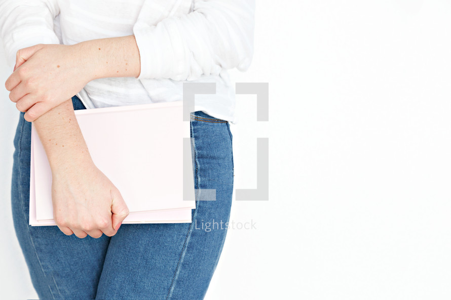 a woman holding a pink notebook